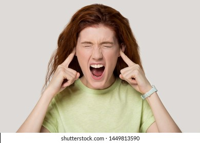Head shot portrait young annoyed stressed red-haired woman sticking plugging fingers in ears, suffering from crazy noisy neighbors or unpleasant sounds, isolated on white grey studio background.