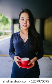 A head shot portrait of a young and attractive Chinese Asian woman in an elegant dark blue dress and holding a red tea cup and saucer. She is smiling enigmatically at the camera.