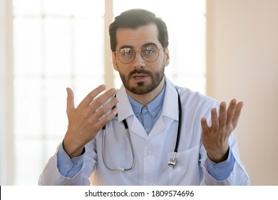Head shot portrait young doctor wearing glasses and white uniform with stethoscope speaking, consulting patient online, looking at camera, making video call, sitting at table in office
