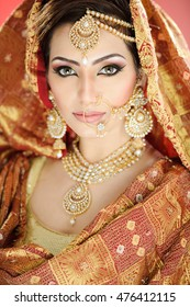 Head shot of a pretty girl in traditional Indian bride costume with heavy jewelry and makeup