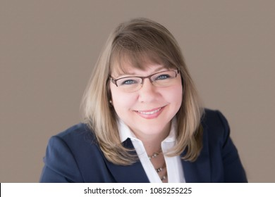 Head shot of professional business woman in her upper forties with blonde hair and blue eyes wearing a blue suit jacket, white blouse, necklace, earrings and glasses. Horizontal landscape orientation.