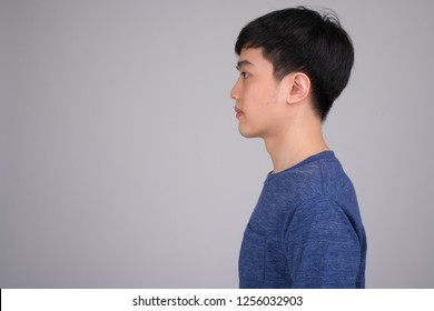 Head shot profile view of young Asian man against white background