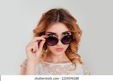 Head shot serious angry bitchy woman wife holding sunglasses down skeptically looking at you isolated light gray wall background, lace dress. Human face expression body language, attitude, perception
