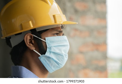 Head shot side view of construction worker seeing outside from construction building window in sad - Industrial worker in a hardhat with medical mask due to coronavirus or covid-19