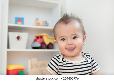Head shot of a silly baby sticking his tongue out. Half Asian baby boy playing in his bedroom. Modern dressed toddler happy and joyful. Bold clothing and room full of toys. Happiest kid.