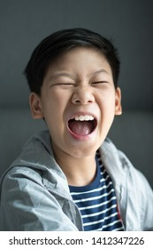 Head shot of smart looking Asian Teen boy 12 years old making silly face, cheerfully shouting or roaring. Overjoyed face expression. Funny posing, Preteen portrait, Cute, Exciting, Tween years.