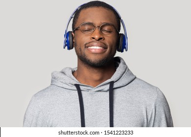 Head shot smiling African American man in headphones enjoying music with closed eyes close up isolated on grey background, handsome young male wearing glasses listening to favorite song