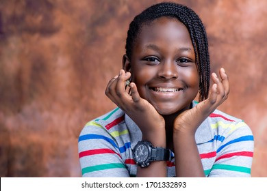 Head shot of smiling Nigerian girl with hands to the face on an abstract background with african hairstyle