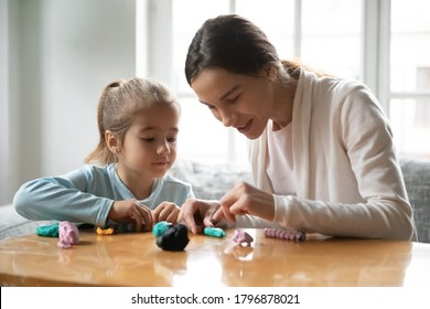 Head shot smiling pretty young mixed race nanny teaching little funny preschool kid girl making figures with colorful playdough, sitting together at table, happy bonding family weekend activity.