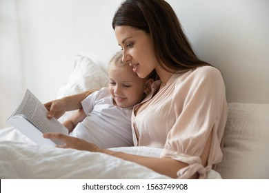Head shot smiling young mommy lying in bed under a blanket with little cute daughter, reading fairytales in morning. Small adorable preschool kid girl looking in book, listening to stories in bedroom.