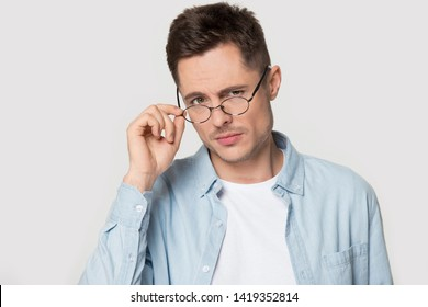Head shot studio portrait distrustful millennial man serious guy staring lowering eyeglasses looking at camera pose on grey white background, mistrust, bad first impression, negative attitude concept