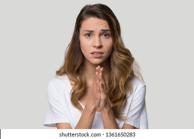Head shot studio portrait millennial woman pose over grey background looking at camera cupped hands in praying gesture feels sad desperate, symbol of asking apologizing, sincere saying please concept