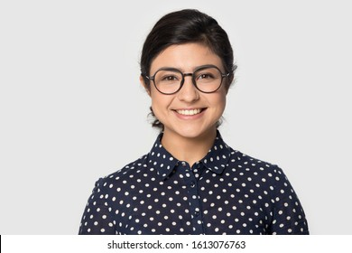 Head shot studio portrait millennial indial pretty smiling girl wearing eyeglasses, looking at camera. Confident student intern, young company worker, female professional isolated on grey background.
