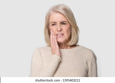 Head shot studio portrait senior blond female pose on grey white background, touches cheek suffering from sudden tooth pain feels unhealthy unhappy need dental service help, medical insurance concept