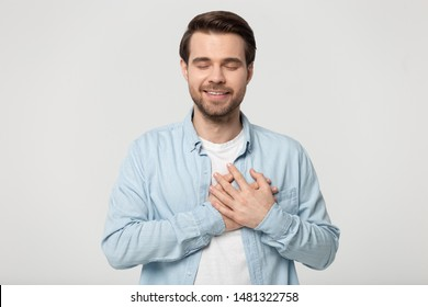 Head shot studio portrait young man with closed eyes folding crossed hands on chest near heart, isolated on grey white background. Thankful guy feeling grateful, positive emotional face expression.