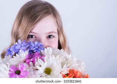 Head shot of twelve-year-old girl with long, dirty blonde hair holding colorful bouquet of daisies over lower face with smiling eyes open against white background