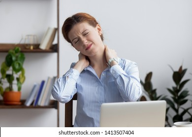 Head shot unhappy businesswoman frowning and massaging tired painful neck sitting at office desk. Upset employee feeling neckache from long time laptop work. Incorrect posture or uncomfortable place