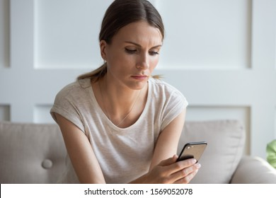 Head shot unhappy thoughtful woman looking at cellphone screen, waiting for call from boyfriend. Pensive millennial lady reading sms or email with bad news, checking social networks, sitting at home.