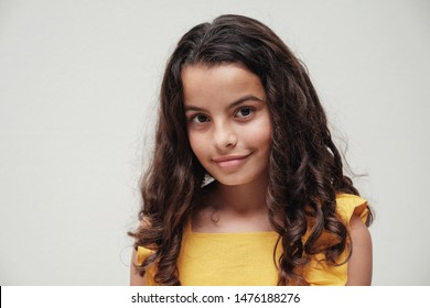 Head shot urban lifestyle portrait of a confident and gorgeous mixed race child face, tween preteen girl with beautiful curly hair wearing yellow summer dress, smiling at camera, youth day