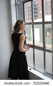 Head shot of a very attractive young woman with blond hair and stunning green eyes. Wearing a black dress, she is waiting and looking out a window.