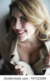 Head shot of a very attractive young woman with blond hair and stunning green eyes. She is wearing a trench coat and showing off a little cleavage.