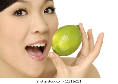 Head shot of woman holding green lime