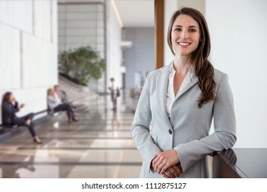 Head shot of a working smiling successful corporate executive beautiful brunette with career, confidence, happiness, joy
