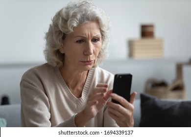 Head shot worried senior mature retired woman holding phone, reading unpleasant news in social media. Unhappy older middle aged grandmother sitting on sofa, received bad news message on smartphone.
