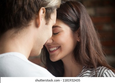 Head shot of young affectionate romantic couple in love. Close up portrait of attractive brunette girl and guy with eyes closed, close to each other. Concept of first kiss, tenderness and amorousness