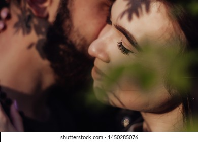 Head shot of young affectionate romantic couple in love. Close up portrait of attractive brunette girl and guy with eyes closed, close to each other. Concept of first kiss, tenderness and amorousness.