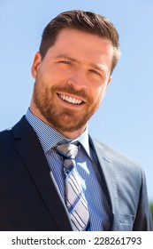 head shot of a young and bearded handsome businessman