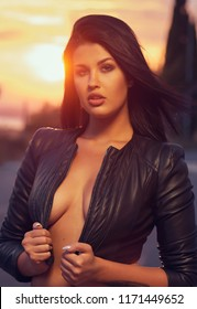Head shot young fashionable beautiful sexy brunette woman wearing leather jacket. Female posing outdoors, evening sky and glowing sun. Girl with sensual decollete, looking at camera. 20 25 years old