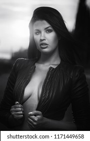 Head shot young fashionable beautiful sexy brunette woman wearing leather jacket. Female posing outdoors. Black and white image. Girl with sensual decollete, looking at camera. 20 25 years old