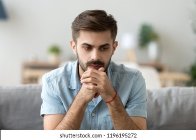 Head shot young millennial serious man sitting on couch home. Portrait of thoughtful pensive handsome serious male student thinking about new idea project analysing planning making decision concept