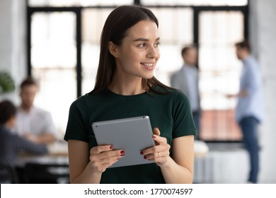 Head shot young secretary manages workday of boss uses tablet device. Businesswoman using pad got good news feels happy. Modern technology, application for online business chat easy and safety concept