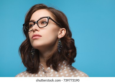 Head shot of young woman in elegant black glasses on blue background.