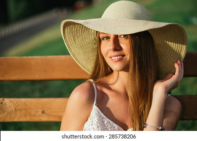 Head shot of young woman posing in park at hat.