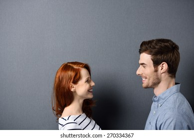 Head and Shoulder Shot of a Happy Young Couple Facing Each Other on a Gray Wall Background, Emphasizing Copy Space.