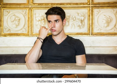 Head and Shoulders of Attractive Young Man Picking Nose with Pinky Finger in Room Decorated with White Marble and Gold Framed Artwork