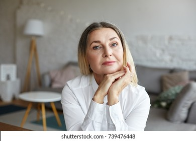 Head and shoulders of beautiful graceful senior woman with healthy wrinkled skin and loose thick hair having rest indoors, posing in modern interior, looking at camera with thoughtful face expression