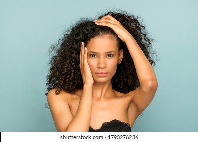 Head and shoulders beauty portrait of a young Afro American girl in a stylish strapless black top posing against a blue studio background with her hands raised to her head looking at camera