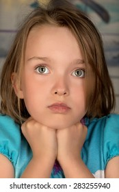 Head and shoulders of a child with pensive expression and hands under her chin