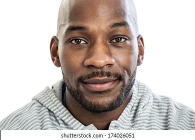 Head and shoulders close up portrait of a handsome black man in late 20s with no expression isolated on white background