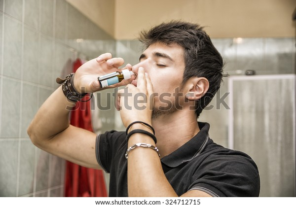 Head and Shoulders Close Up of Young Attractive Man with Dark Hair Sniffing Nose Spray with Eyes Closed in Home Bathroom