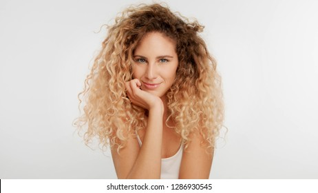 head and shoulders plan of blonde wooman with big curly hair in studio on white watching directly to the camera has a sort of flirt look