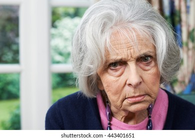 Head And Shoulders Portrait Of Angry Senior Woman At Home