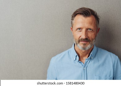 Head and shoulders portrait of an attractive bearded middle-aged man looking into the camera over a grey studio background with copy space