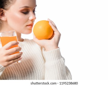 head and shoulders portrait of attractive beautiful young caucasian woman isolated on white studio shot drinking orange juice face skin holding orange