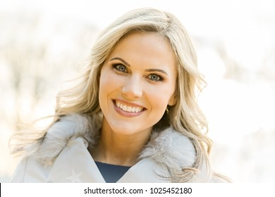 Head and shoulders portrait of a beautiful mid 30s caucasian blond woman wearing a winter coat outside on a cold day, smiling looking at camera