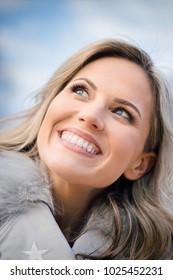 Head and shoulders portrait of a beautiful mid 30s woman outdoors wearing a winter coat looking up at the blue sky